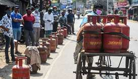 People wait with their empty domestic gas cylinders outside a delivery centre to collect refilled cy