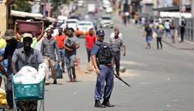 A police officer looks on as locals go on their daily business on the first day of a nationwide lock