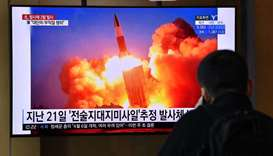 A man watches a news broadcast showing file footage of a North Korean missile test, at a railway sta
