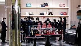 Staff members wearing face masks get ready for a ceremony before a Gucci store inside a shopping mal