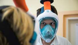 Medical workers from Motol hospital wear snorkel masks transformed into high-grade protection by res