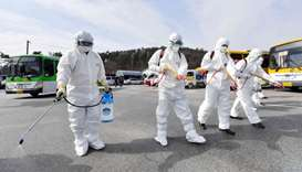 South Korean government officials wearing protective gear spray disinfectant as part of preventive m