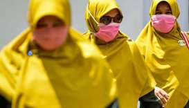Women wearing face masks walk in a public area in Banda Aceh on March 2