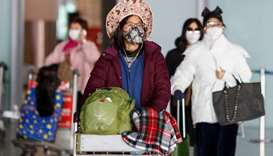 People wear face masks upon their arrival at Beijing Capital Airport, as the country is hit by an ou