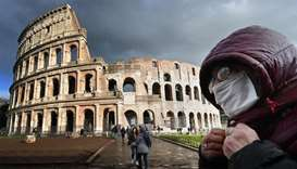 A man wearing a protective mask passes by the Coliseum in Rome amid fear of Covid-19 epidemic