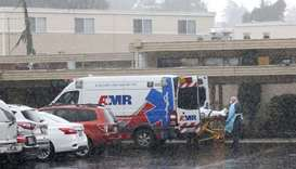 A patient is put into an ambulance during the pouring rain outside the Life Care Center of Kirkland
