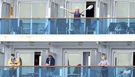 A woman gestures as other people look on from aboard the Grand Princess cruise ship, operated by Pri