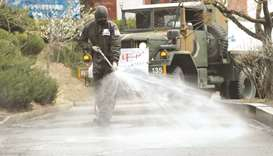 A South Korean soldier sprays disinfectants at an apartment complex which is under cohort isolation