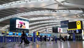 Travellers wearing face coverings walk with their luggage in the almost deserted departures hall at
