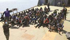 Rescued migrants sit aboard a Libyan coastguard vessel arriving at the capital Tripoli's naval base,