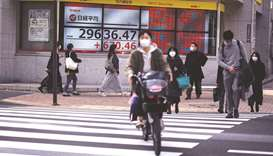 Pedestrians walk in front of an electronic quotation board displaying the numbers of share prices in