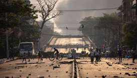 People walk past makeshift barricades set up by protesters to block a road during demonstrations aga