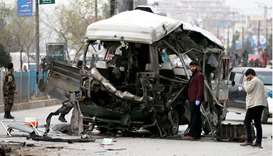 Afghan officials inspect a damaged minibus after a blast in Kabul, Afghanistan