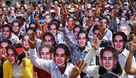 Protesters wearing masks depicting ousted leader Aung San Suu Kyi, flash three-finger salutes as the