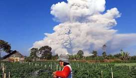 A farmer tends to a farm as Mount Sinabung spews ash into the sky, as seen from Karo, North Sumatra