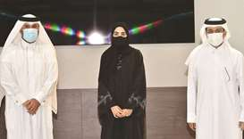 The QU president and dean of the College of Arts and Sciences honour student Noura al-Ansari.