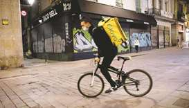 A Glovo courier rides through Barcelona. Spain aims to bolster protections for service sector worker