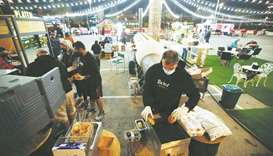 A vendor prepares burgers at Radical Barbecue, a food stand, at Al Aali Mall amid the coronavirus di