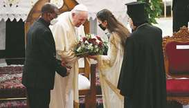 An Iraqi woman offers Pope Francis a bouquet of flowers upon his arrival at the Syro-Catholic Cathed