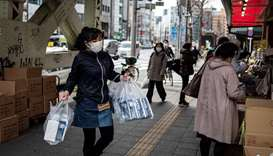 A vendor replenishes her stall with boxes of face masks in Tokyo