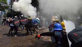 Protesters react after tear gas is fired by police during a demonstration against the military coup