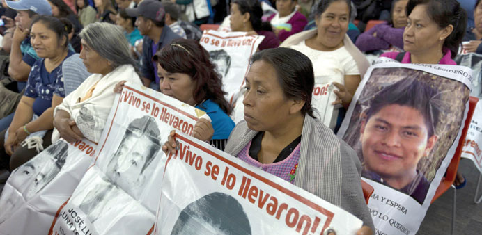 Relatives and friends of the 43 missing students wait before experts of the Inter-American Commissio
