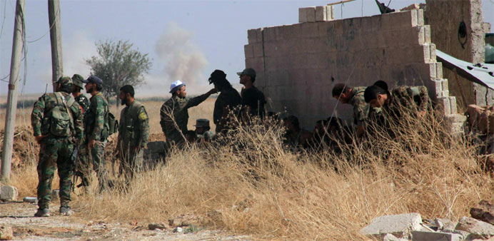 Syrian regime soldiers rest in an area around Kweyris military airport, in the eastern Aleppo provin