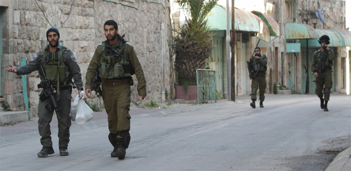 Israeli security forces walk near the site of a Palestinian attack