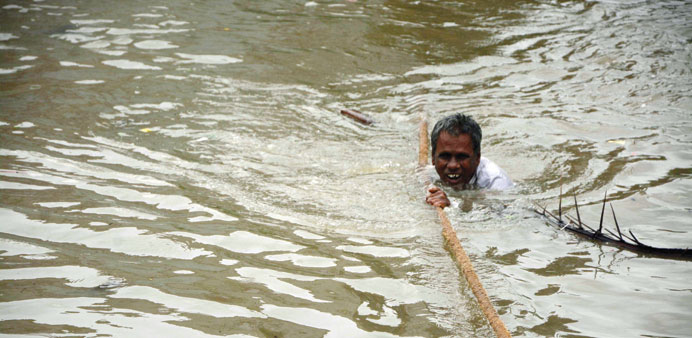 A man clings to a rope as he makes his way through floodwaters in Chennai.