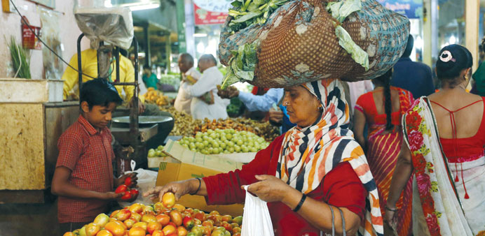 A woman carrying cabbage leaves buys tomato at a market in Ahmedabad. Prices of vegetables like onio