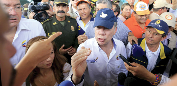 Colombia's President Juan Manuel Santos speaks with a family deported from Venezuela during a visit