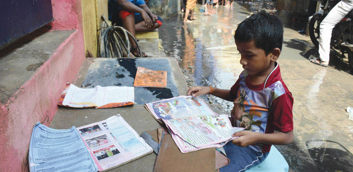 A boy puts his school books out to dry as floodwaters recede in Chennai.