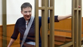 Ukrainian military pilot Nadiya Savchenko looking out from a defendants' cage after the first day of