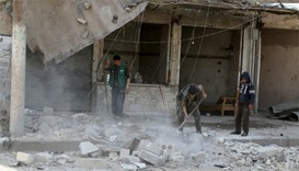Residents remove debris after an airstrike in Aleppo