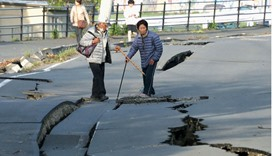 Local residents look at cracks caused by an earthquake on a road in Mashiki town, Kumamoto prefectur