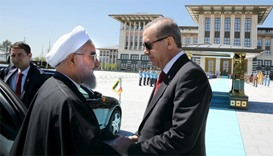 Turkish President Tayyip Erdogan (R) shakes hands with his Iranian counterpart Hassan Rouhani
