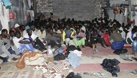 Illegal migrants sit huddled at a hideout after Libyan security forces conducted a raid in Tripoli,