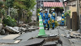 Policemen search for missing people in a damaged neighbourhood following earthquakes