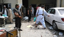 Pakistani security officials inspect the site of a suicide bomb attack on a government building in M