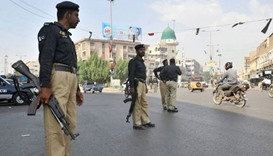 Police guard the street in Orangi after the attack.