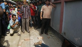 People gather around the body of Bangladeshi professor Rezaul Karim Siddique after he was hacked to