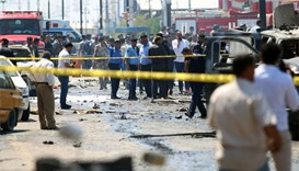 Iraqi security forces and emergency personnel stand at the site of a suicide attack in the southern