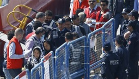 Migrants are escorted by Turkish police officers as they arrive in the Turkish coastal town of Dikil