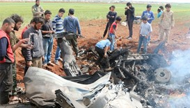 Rebel fighters and civilians gather around the wreckage of a Syrian warplane that was shot down