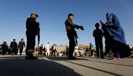 An Afghan family waits as policemen block the road near the site of of suicide bomb attack in Kabul