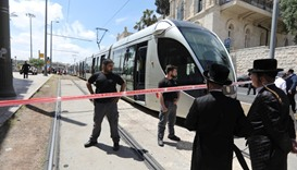 Israeli policemen block a road where the light train passes following a stabbing attack just outside