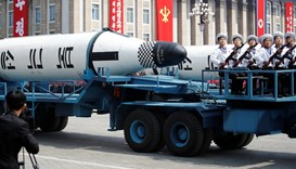 Military vehicles carry missiles with characters reading 'Pukkuksong' during a military parade
