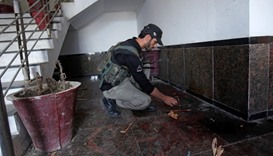 A policeman searches for evidence at the dorm where Mashal Khan, accused of blasphemy, was killed by