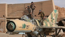 Syrian Democratic Forces (SDF) fighters gesture while posing on a damaged airplane inside Tabqa mili