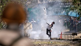 A Kashmiri student throws back a tear-gas canister fired by Indian police during a protest